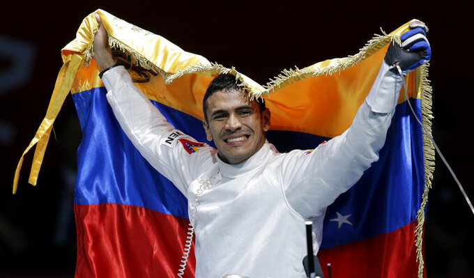 FILE - In this Aug. 1, 2012, file photo, Venezuela's Ruben Limardo Gascon celebrates after defeating Norway's Bartosz Piasecki in the gold medal match in men's individual epee fencing competition at the 2012 Summer Olympics in London. Limardo, who won the Olympic gold in London 2012, is currently delivering food for an online platform in Poland because of the ongoing coronavirus pandemic. (AP Photo/Dmitry Lovetsky, File)