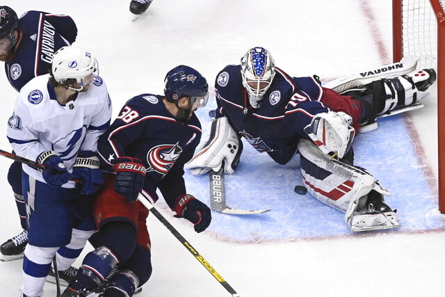 Columbus Blue Jackets goaltender Joonas Korpisalo (70) makes a stop as Tampa Bay Lightning center Brayden Point (21) and Blue Jackets center Boone Jenner (38) look for a rebound during the third period of Game 3 of an NHL hockey first-round playoff series, Saturday, Aug. 15, 2020, in Toronto. (Nathan Denette/The Canadian Press via AP)