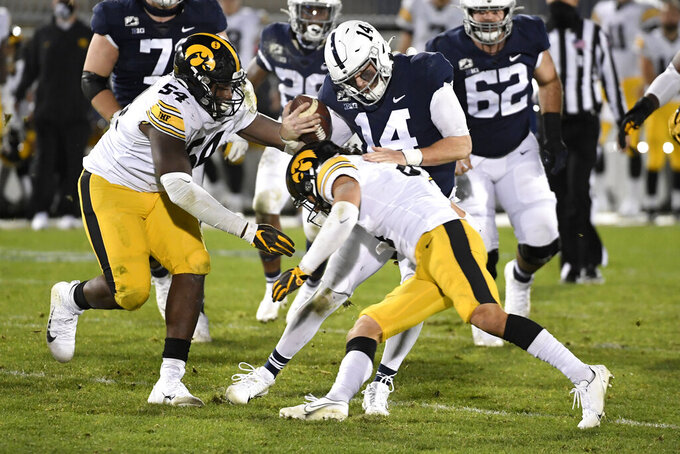 Iowa defenders Daviyon Nixon (54)and Dane Belton (4) tackle Penn State quarterback Sean Clifford (14) during an NCAA college football game in State College, Pa., on Saturday, Nov. 21, 2020.Iowa defeated Penn State 41-21. (AP Photo/Barry Reeger)