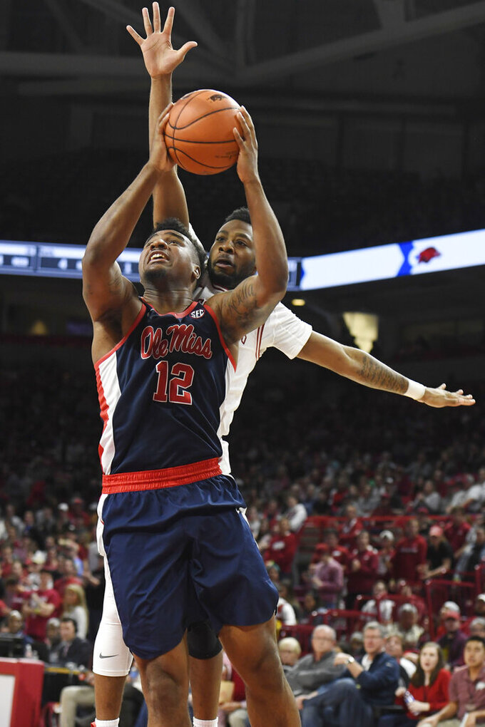Mississippi forward Bruce Stevens (12) tries to get past Arkansas defender Keyshawn Embery-Simpson during the second half of an NCAA college basketball game, Saturday, March 2, 2019 in Fayetteville, Ark. (AP Photo/Michael Woods)