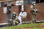South African National Defense Forces patrol the Men's Hostel in the densely populated Alexandra township east of Johannesburg, Saturday, March 28, 2020, enforcing a strict lockdown in an effort to control the spread of the coronavirus. The new coronavirus causes mild or moderate symptoms for most people, but for some, especially older adults and people with existing health problems, it can cause more severe illness or death.(AP Photo/Jerome Delay)