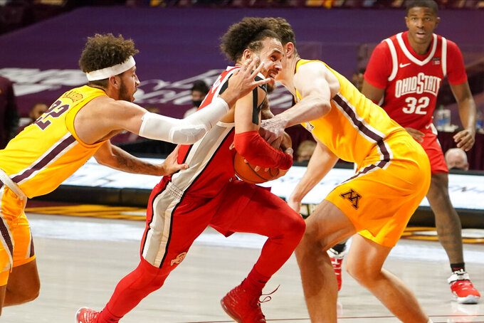 Ohio State's Duane Washington Jr., center, drives between Minnesota's Gabe Kalscheur, left, and Liam Robbins in the second half of an NCAA college basketball game Sunday, Jan. 3, 2021, in Minneapolis. (AP Photo/Jim Mone)