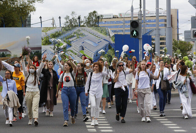 Belarusian women rally in solidarity with protesters injured in the latest rallies against the results of the country's presidential election in Minsk, Belarus, Thursday, Aug. 13, 2020. Hundreds of people were back on the streets of Belarus' capital on Thursday morning, forming long
