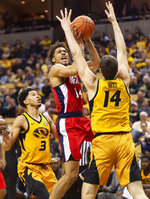Mississippi's KJ Buffen, center, shoots between Missouri's Reed Nikko, right, and Ronnie Suggs, left, during the first half of an NCAA college basketball game Saturday, March 9, 2019, in Columbia, Mo. (AP Photo/L.G. Patterson)