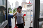 A woman wearing a face mask to help curb the spread of the coronavirus gets fever checked before going into the Pyongyang Railway Station in Pyongyang, North Korea, Thursday, Aug. 13, 2020. (AP Photo/Cha Song Ho)
