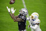 Las Vegas Raiders tight end Darren Waller (83) catches a pass before running it in for a touchdown against Los Angeles Chargers cornerback Michael Davis (43) during the first half of an NFL football game, Thursday, Dec. 17, 2020, in Las Vegas. (AP Photo/Isaac Brekken)