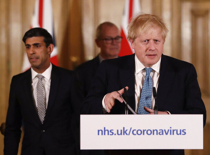 FILE - In this file photo dated Tuesday, March 17, 2020, Britain's Chancellor Rishi Sunak, left, and Prime Minister Boris Johnson arrive for a press briefing about the ongoing situation with the COVID-19 coronavirus outbreak, inside 10 Downing Street in London.  With British Prime Minister Boris Johnson hospitalized and in intensive care Wednesday April 8, 2020, after contracting the new coronavirus, Sunak is among key players in Johnson's Cabinet who will be directing Britain's response to the highly contagious COVID-19 coronavirus, while their leader is being treated. (AP Photo/Matt Dunham, FILE)