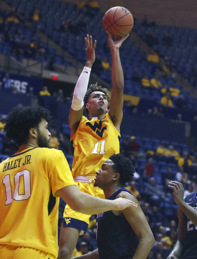 West Virginia forward Emmitt Matthews Jr. (11) shoots while defend by Kansas State forward Xavier Sneed (20) during the second half of an NCAA college basketball game Monday, Feb. 18, 2019, in Morgantown, W.Va. (AP Photo/Raymond Thompson)