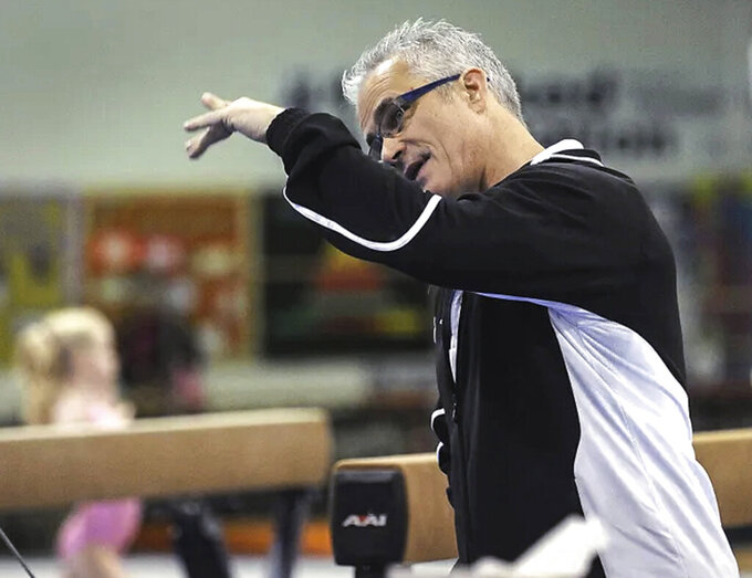 John Geddert watches his gymnastics students during practice in December 2011. Geddert, a former U.S. Olympics gymnastics coach with ties to disgraced sports doctor Larry Nassar, killed himself Thursday, Feb. 25, 2021, hours after being charged with turning his Michigan gym into a hub of human trafficking by coercing girls to train and then abusing them. Geddert faced 24 charges that could have carried years in prison had he been convicted. (Greg DeRuiter/Lansing State Journal via AP)