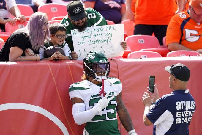 New York Jets running back Ty Johnson (25) has security take his picture with New York Jets fans prior to an NFL football game against the Denver Broncos, Sunday, Sept. 26, 2021, in Denver. (AP Photo/David Zalubowski)