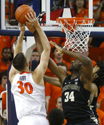 Wake Forest forward Sunday Okeke (34) blocks a shot by Virginia forward Jay Huff (30) during the first half of an NCAA college basketball game in Charlottesville, Va., Tuesday, Jan. 22, 2019. (AP Photo/Steve Helber)