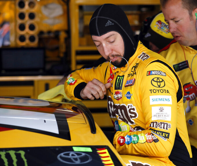 Driver Kyle Busch climbs into his car to practice for the NASCAR Cup Series auto race at Kansas Speedway in Kansas City, Kan., Friday, May 10, 2019. Busch leads the series in points. (AP Photo/Colin E. Braley)