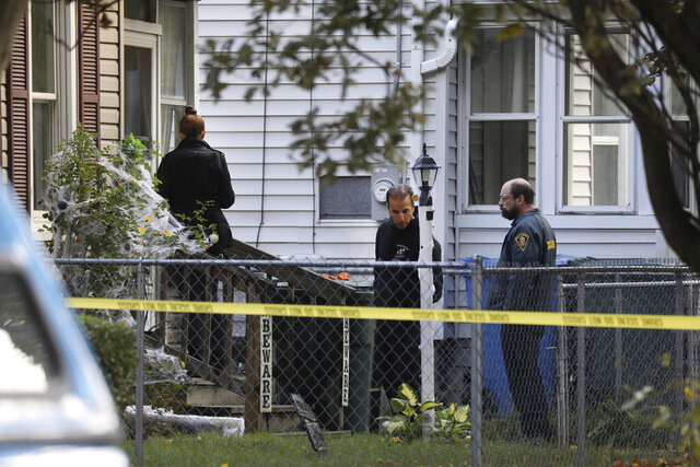 FILE - In this Saturday, Sept. 19, 2020, file photo, Rochester police search for clues and evidence as they look over the area of a home after a fatal shooting at a backyard house party in Rochester, N.Y. On Thursday, Oct. 22, 2020, police investigating the mass shooting at a crowded house party that killed two teenagers and wounded 14 others, joined with grieving parents to plead for witnesses to come forward as they announced a $10,000 reward. (Tina MacIntyre-Yee/Democrat & Chronicle via AP, File)