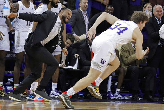 Washington assistant coach Will Conroy, left, celebrates on the bench after forward Reagan Lundeen (34) tipped in a shot against California during the second half of an NCAA college basketball game Saturday, Feb. 22, 2020, in Seattle. Washington won 87-52. (AP Photo/Ted S. Warren)