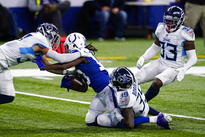 Indianapolis Colts wide receiver T.Y. Hilton (13) is tackled by Tennessee Titans defensive back Chris Jackson (35) and strong safety Amani Hooker (37) in the second half of an NFL football game in Indianapolis, Sunday, Nov. 29, 2020. (AP Photo/Darron Cummings)