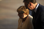German Chancellor Angela Merkel, center, is accompanied by Serbia's president Aleksandar Vucic during her visit to Belgrade, Serbia, Monday, Sept. 13, 2021. Merkel is on a farewell tour of the Western Balkans, as she announced in 2018 that she wouldn't seek a fifth term as Germany's Chancellor. (AP Photo/Marko Drobnjakovic)