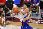 Oklahoma forward Jalen Hill, top, catches the ball and lands on Houston Baptist guard Hunter Janacek, right, in the first half of an NCAA college basketball game Saturday, Dec. 19, 2020, in Norman, Okla. (AP Photo/Sue Ogrocki)