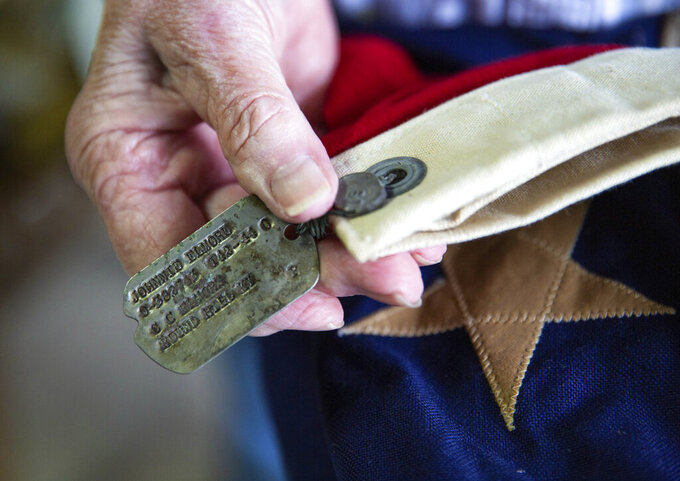 Velda Alexander of Bowling Green, Ky., holds the dog tags of her father U.S. Army 2nd Lt. Johnnie Elmore which are tied to a folded American flag while going through the contents of his military footlocker trunk in her garage on Wednesday, Sept. 15, 2021, after she and her family found the trunk in her grandmother's old country store in Round Hill last week after it had been missing for nearly 77 years. Elmore, who graduated ROTC at Western Kentucky University in 1941, was killed in action in December 1944 at the age of 31 while based in France and England during World War II. The trunk contains a World War II uniform, a folded American flag, a Purple Heart and other medals and patches, dog tags, love letters to his soon-to-be wife Irene Martin, diaries and more. (Grace Ramey/Bowling Green Daily News via AP)/Daily News via AP)/Daily News via AP)