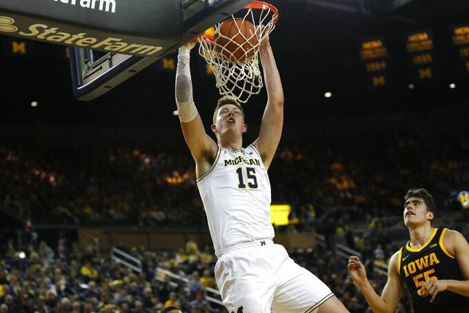 Michigan center Jon Teske (15) dunks against Iowa center Luka Garza (55) in the first half of an NCAA college basketball game in Ann Arbor, Mich., Friday, Dec. 6, 2019. (AP Photo/Paul Sancya)