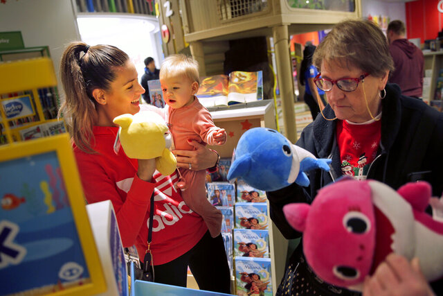 FILE - In this Dec. 9, 2019, file photo Melissa Rogan, left, and her daughter Renee, 9-months-old, browse the new Toys R Us store at a mall in Paramus, N.J. On Tuesday, Feb. 25, 2020, the Conference Board reports on U.S. consumer confidence for February. (AP Photo/Seth Wenig, File)
