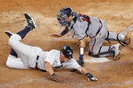 New York Yankees DJ LeMahieu, left, scores on Aaron Hick's fourth-inning double as Atlanta Braves catcher Travis d'Arnaud (16) is late with the tag in a baseball game, Wednesday, Aug. 12, 2020, in New York. (AP Photo/Kathy Willens)