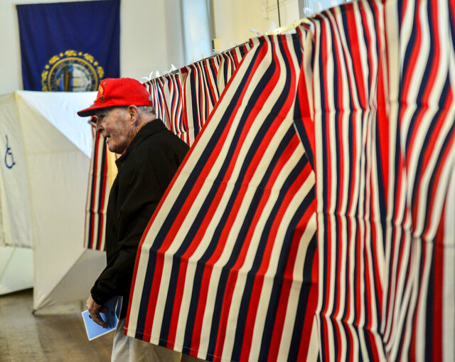William J. Patenaude, a Korean and Vietnam veteran and resident of Chesterfield, N.H., leaves the voting booth with his ballot in hand at the Chesterfield, N.H., Polling Station inside the Town Hall during the New Hampshire presidential primary elections, Tuesday, Feb. 11, 2020. (Kristopher Radder/The Brattleboro Reformer via AP)