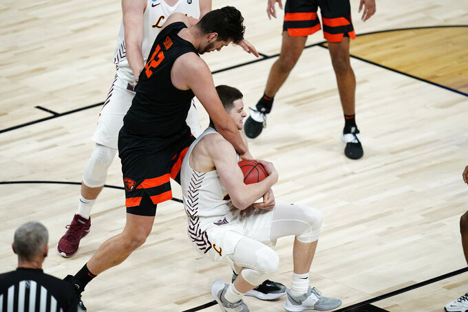 Loyola Chicago guard Tate Hall fights for a loose ball with Oregon State center Roman Silva (12) during the first half of a Sweet 16 game in the NCAA men's college basketball tournament at Bankers Life Fieldhouse, Saturday, March 27, 2021, in Indianapolis. (AP Photo/Darron Cummings)