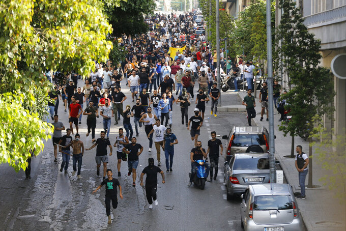 Shiite Hezbollah and Amal Movement groups run as they shout slogans against anti-government protesters, in downtown Beirut, Lebanon, Saturday, June 6, 2020. Hundreds of Lebanese demonstrators gathered in central Beirut Saturday, hoping to reboot nationwide anti-government protests that began late last year amid an unprecedented economic and financial crisis. (AP Photo/Bilal Hussein)
