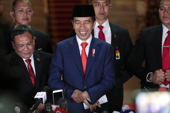 Indonesian President Joko Widodo, center, smiles as he speaks to the media upon arrival after his inauguration for his second term, at Merdeka Palace in Jakarta, Indonesia, Sunday, Oct. 20, 2019. Widodo, who rose from poverty and pledged to champion democracy, fight entrenched corruption and modernize the world's most populous Muslim-majority nation, was sworn in Sunday for his second and final five-year term with a pledge to take bolder actions. (AP Photo/Dita Alangkara)