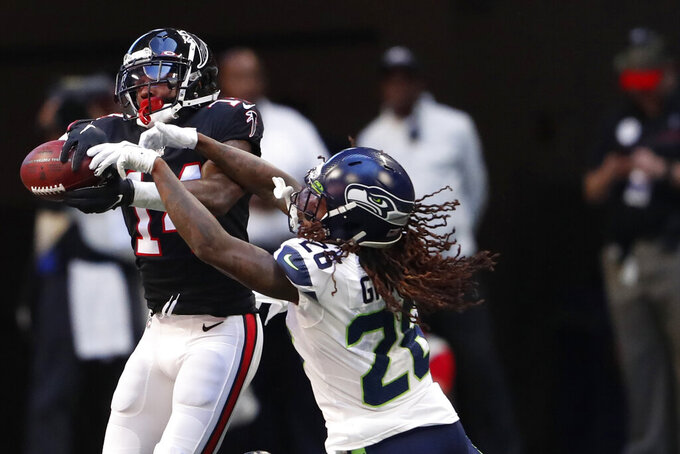 Atlanta Falcons wide receiver Justin Hardy (14) makes the catch against Seattle Seahawks cornerback Shaquill Griffin (26) during the first half of an NFL football game, Sunday, Oct. 27, 2019, in Atlanta. (AP Photo/John Bazemore)