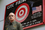 FILE - In this July 16, 2019, file photo, Doug Tangen, a firearms instructor at the Washington State Criminal Justice Training Commission, poses for a photo near a sign outside a firing range used in the state's Basic Law Enforcement Academy in Burien, Wash. Tangen says the facility has had trouble getting the supply of ammunition that they need for firearms training due to shortages blamed on the COVID-19 pandemic and record sales of firearms. (AP Photo/Ted S. Warren, File)