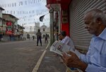 A man reads a newspaper as air force officers stand guard outside St. Anthony's Shrine in Colombo, Sri Lanka, Friday, April 26, 2019. (AP Photo/Gemunu Amarasinghe)