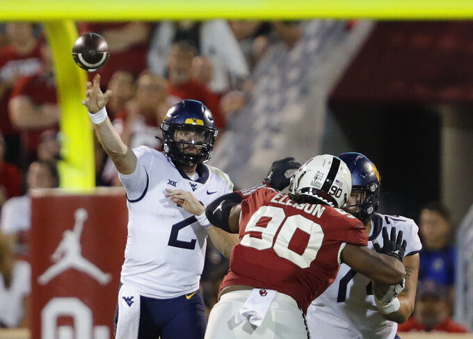 West Virginia quarterback Jarret Doege (2) passes against Oklahoma during the second half of an NCAA college football game in Norman, Okla., Saturday, Sept. 25, 2021. (AP Photo/Alonzo Adams)