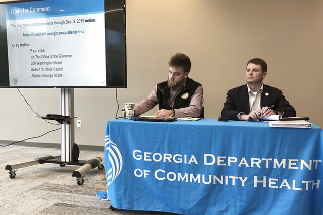 In this photo taken on Nov. 22, 2019, Ryan Loke, left, Gov. Brian Kemp's health policy adviser, and Blake Fulenwider, the chief health policy officer for the Georgia Department of Community Health, attend a public hearing in Kennesaw, Ga., about Kemp's recent health care proposals.  Georgia could be the first state to test proposals from the Trump administration that would dramatically change the federal market for health insurance.  (AP Photo/Sudhin Thanawala)