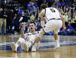 Wofford's Fletcher Magee, left, reacts after drawing a foul on a 3-point shot as Storm Murphy (5) helps him up during the first half against Seton Hall in a first-round game in the NCAA men's college basketball tournament in Jacksonville, Fla., Thursday, March 21, 2019. (AP Photo/Stephen B. Morton)