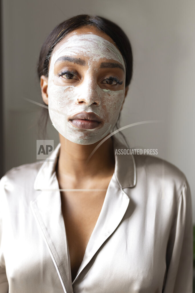 Woman with beauty mask on face waiting to dry at home