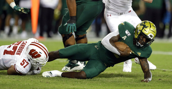 South Florida running back Jordan Cronkrite, right, gets tripped up by Wisconsin linebacker Jack Sanborn (57) at the end of a run during the first half of an NCAA college football game Friday, Aug. 30, 2019, in Tampa, Fla. (AP Photo/Chris O'Meara)