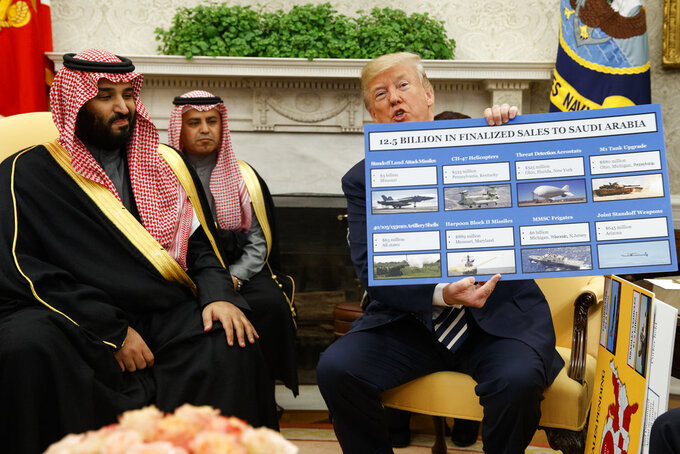 FILE - In this March 20, 2018 file photo, President Donald Trump shows a chart highlighting arms sales to Saudi Arabia during a meeting with Saudi Crown Prince Mohammed bin Salman in the Oval Office of the White House, in Washington. Salman's first trip abroad since the killing of Saudi writer Jamal Khashoggi will offer an early indication of whether he will face any repercussions. The prince is visiting close allies in the Middle East before attending the Group of 20 Summit in Argentina, where he will come face to face with Trump, who appears keen to preserve their friendship, as well as European leaders and Turkey's president, who has stepped up pressure on the kingdom. (AP Photo/Evan Vucci, File)