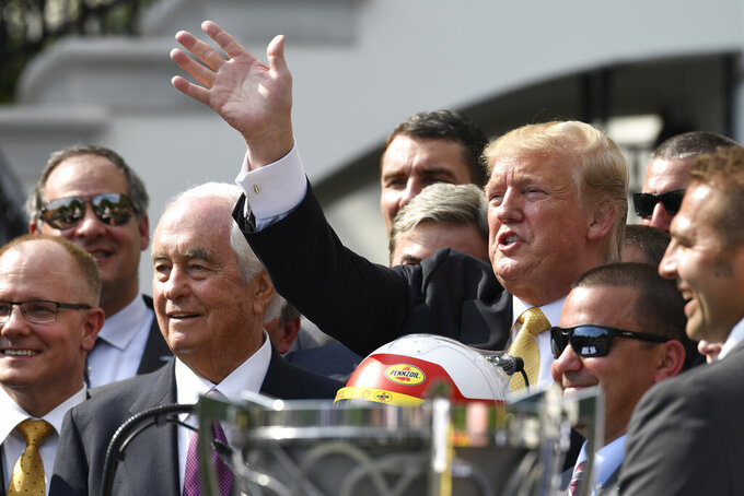 President Donald Trump waves as he poses for pictures during an event to welcome Joey Logano, the 2018 NASCAR Cup Series Champion, to the South Lawn of the White House in Washington, Tuesday, April 30, 2019. Penske team owner Roger Penske is third from left. (AP Photo/Susan Walsh)