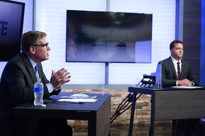 U.S. Sen. Mark Warner, D-Va., left, gestures during a debate with Republican challenger Daniel Gade, right, at a television studio Tuesday Oct. 13, 2020, in Richmond, Va. (AP Photo/Steve Helber)