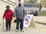 Tim and Pat Tompkins pause for a picture on their way to early vote in Bettendorf, Iowa, Friday, Oct. 16, 2020. Tompkins said he and his wife, Pat, were concerned about coronavirus exposure in bigger crowds and brought their own sanitizer, but were determined to vote. (AP Photo/Geoff Mulvihill)