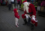 Fredy Parra, dressed as Santa Claus, speaks to a girl at a Christmas fair in Caracas, Venezuela, Dec. 18, 2020. For more than 10 years, children have had their picture taken with Parra at the fair for a small fee. (AP Photo/Ariana Cubillos)