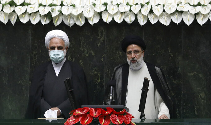 President Ebrahim Raisi, right, takes his oath as president, as Judiciary Chief Gholamhossein Mohseni Ejehi listens in a ceremony at the parliament in Tehran, Iran, Thursday, Aug. 5, 2021.  Raisi, a protégé of Iran's supreme leader, completes hard-liners' dominance of all branches of government in the Islamic Republic. (AP Photo/Vahid Salemi)