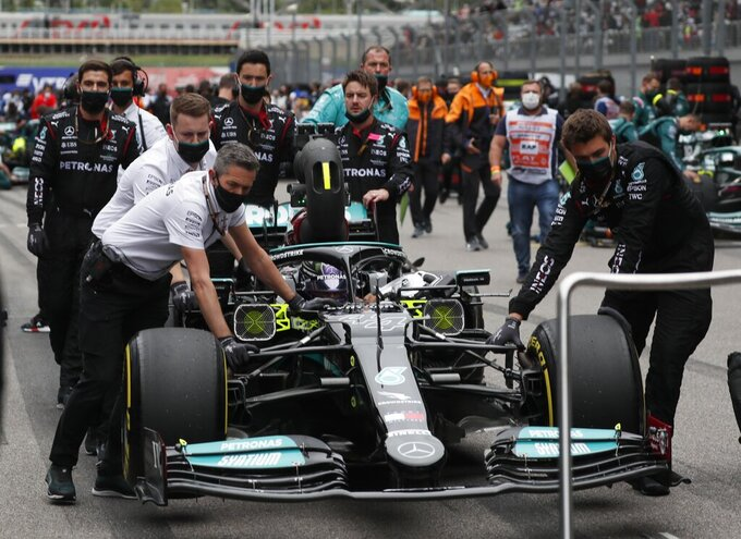 Mechanics push the car of Mercedes driver Lewis Hamilton of Britain on the grid before the Russian Formula One Grand Prix at the Sochi Autodrom circuit, in Sochi, Russia, Sunday, Sept. 26, 2021. (Yuri Kochetkov/Pool Photo via AP)