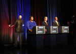 Gubernatorial candidates for Georgia from left; Democrat Stacey Abrams, Republican Secretary of State Brian Kemp, and Libertarian Ted Metz, right, wait as a stage crew member looks for the source of a fire alarm that sounded during a debate Tuesday, Oct. 23, 2018, in Atlanta. (AP Photo/John Bazemore)