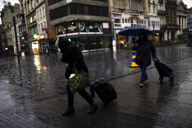 Passers-by, wearing face masks to prevent the spread of the coronavirus COVID-19, walk along a commercial area during a rainy autumn day in Brussels, Tuesday, Nov. 10, 2020. This autumn, Belgium was the European country with the highest number of coronavirus cases per 100,000 cases at some point but the situation has been gradually improving over the past seven days.(AP Photo/Francisco Seco)