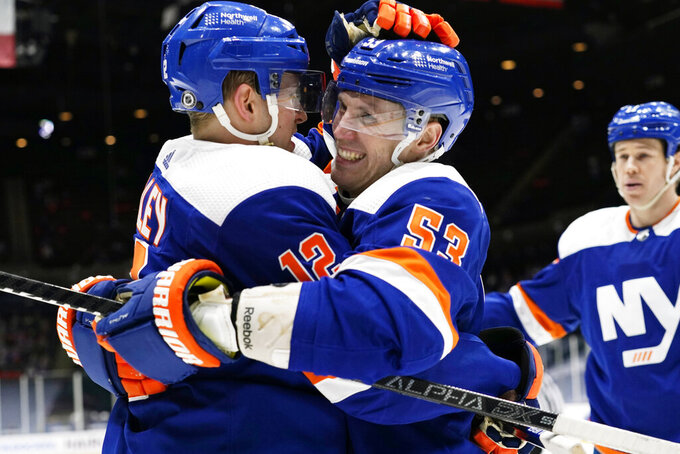 New York Islanders right wing Josh Bailey (12) celebrates with center Casey Cizikas (53) as left wing Matt Martin (17) watches, after Bailey scored a goal during the second period of the team's NHL hockey game against the New Jersey Devils, Thursday, March 11, 2021, in Uniondale, N.Y. (AP Photo/Kathy Willens)