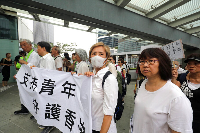 CORRECTS FIRST NAME OF THE ACTRESS - Veteran actress and singer Deanie Ip, center, wears a mask as she holds a banner in support of young people during a march in Hong Kong on Wednesday, July 17, 2019. Some 2,000 Hong Kong senior citizens, including the popular actress, marched Wednesday in a show of support for youths at the forefront of monthlong protests against a contentious extradition bill in the semi-autonomous Chinese territory.(AP Photo)