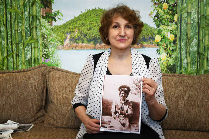 In this photo taken on Sunday, Feb. 10, 2019, Tatyana Rybalchenko, who worked as a nurse during the Soviet campaign in Afghanistan between 1986 and 1988, holds a photo of her taken in June 1986 in Kabul, Afghanistan, during her interview with The Associated Press in Moscow, Russia. As Russia this week marks the 30th anniversary of the withdrawal of the Soviet troops, the memories of the war are still fresh for female nurses and clerks and shopkeepers, mostly young and single, who were thrust into the disastrous campaign that came to known as Russia's Vietnam. (AP Photo/Alexander Zemlianichenko)
