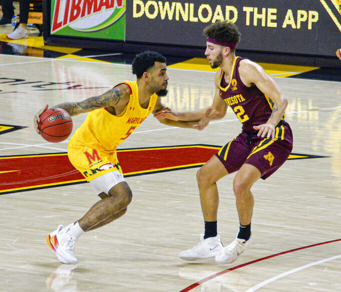 Maryland guard Eric Ayala, left, drives the floor against Minnesota during the first half  of an NCAA college basketball game, Sunday, Feb. 14, 2021, in College Park, Md. (Kevin Richardson/The Baltimore Sun via AP)